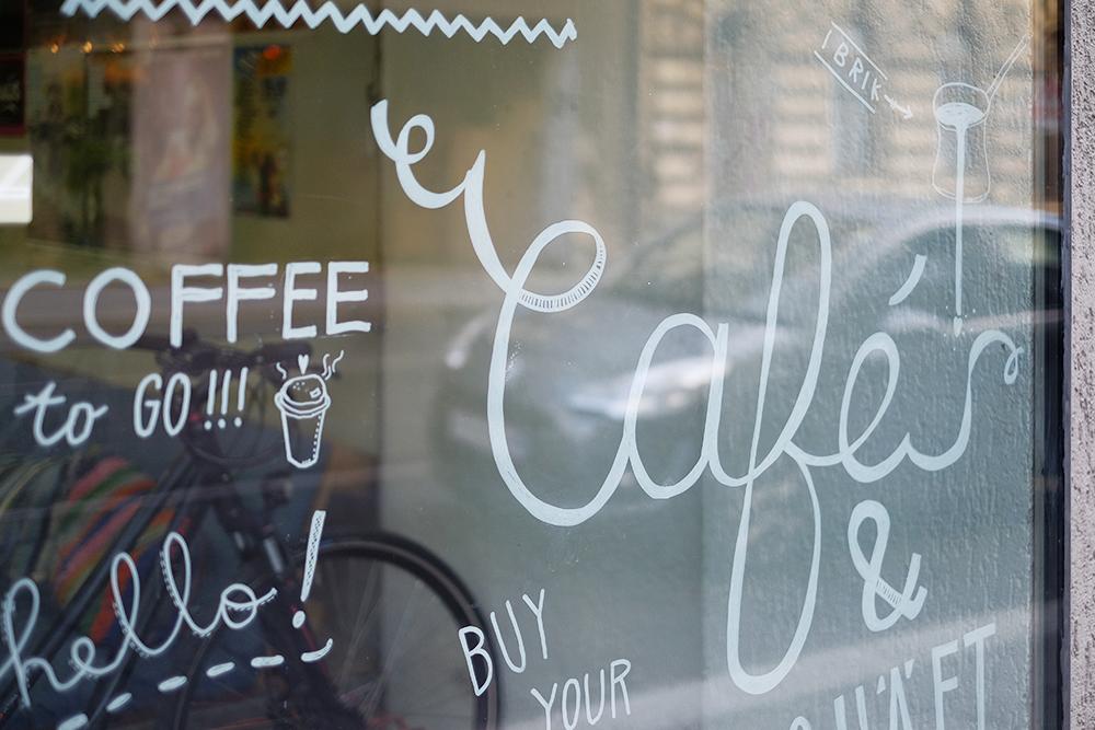 Schnörkel an der Fensterscheibe: Café & Gschäft